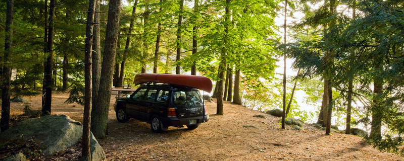 A car with a canoe on the roof parked in a wooded campsite