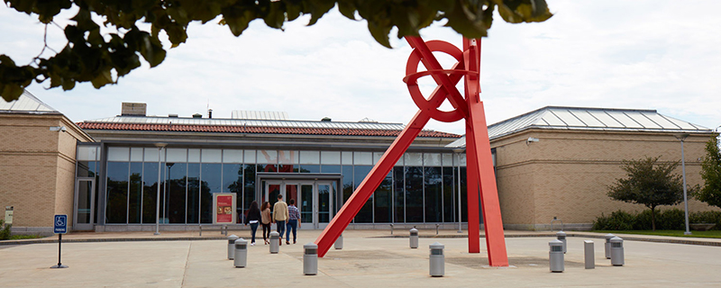 A group of people entering the Currier Museum, with red sculpture outside