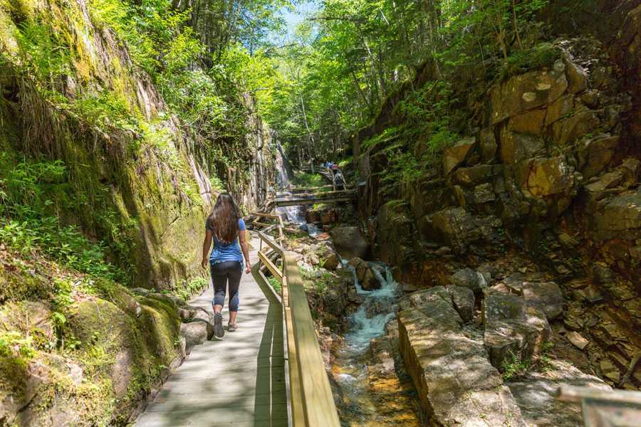 Woman walking down a boardwalk next to waterfalls