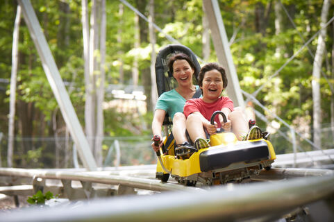 A woman and boy riding a mountain coaster