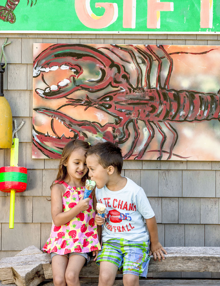 Two kids eating ice-cream outside by a lobster painting
